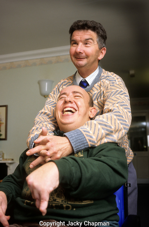 Two disabled friends warmly smiling and laughing together while posing for a photograph