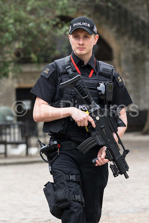An armed police officer from the City of London Police force patrols at the Tower of London  in London, England on September 05, 2018.