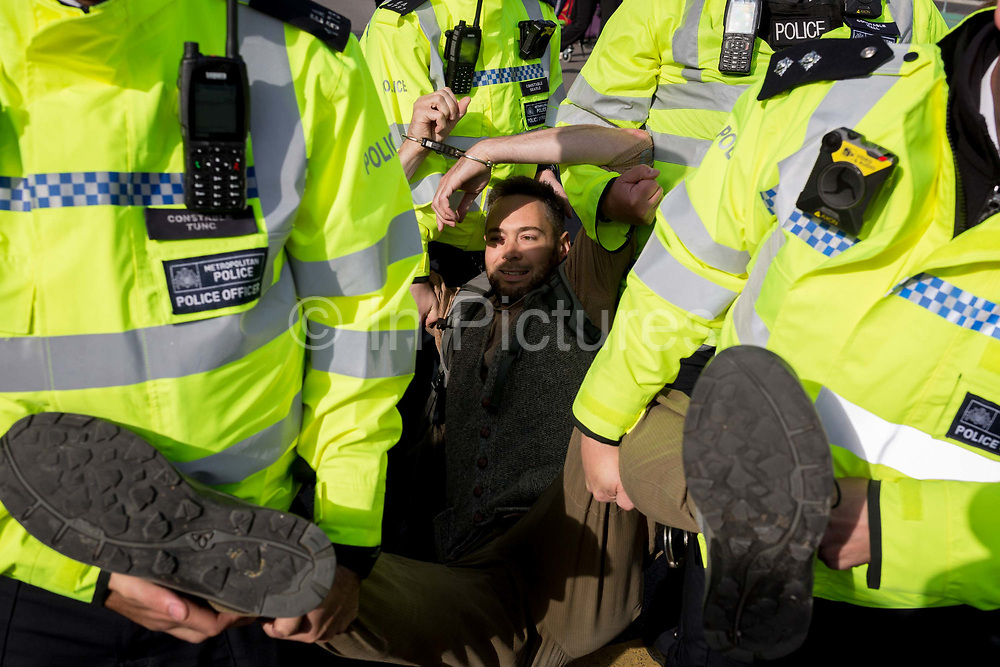 An environmental activist is arrested under the Public Order Act while protesting about Climate Change during the occupation of City Airport Londons Business Travel hub in east London, the fourth day of a two-week prolonged worldwide protest by members of Extinction Rebellion, on 10th October 2019, in London, England.