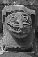The Stone Bestiary - Black and white photo art print of Norman Romanesque exterior corbel no 37 - sculpture of a grotesque head with interlocking teeth. The Norman Romanesque Church of St Mary and St David, Kilpeck Herefordshire, England. Built around 1140 .<br /> <br /> Visit our LANDSCAPE PHOTO ART PRINT COLLECTIONS for more wall art photos to browse https://funkystock.photoshelter.com/gallery-collection/Places-Landscape-Photo-art-Prints-by-Photographer-Paul-Williams/C00001WetsxVxNTo