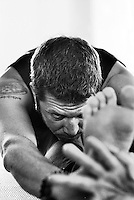 Close up of a man in a deep forward yoga bend.