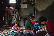 L-R: Shugufta, 29, Zainab, 10 months, Muzamil, 6, Azra, 5, and Igra, 8, in their temporary shelter in Narbal village, Jammu and Kashmir, India, on 24th March 2015. When the floods hit in the middle of the night, Shugufta and her family had to walk 5 miles to find shelter. Save the Children supported the family with shelter kits, blankets, hygiene items, food and tarpaulin, which they have used to build a temporary shelter next to their crumbled home. Photo by Suzanne Lee for Save the Children