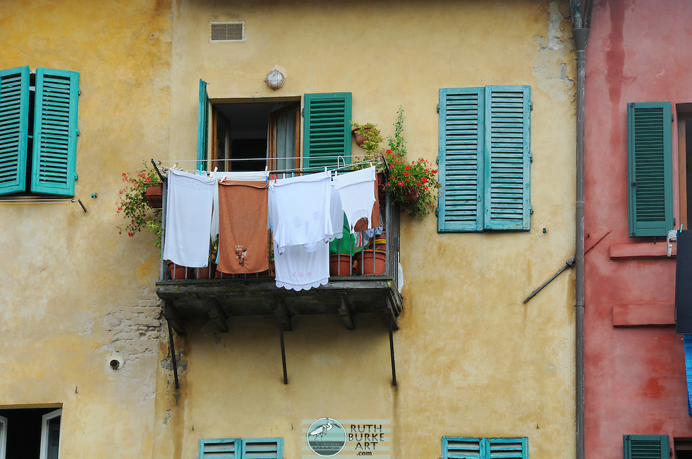 Clothes hanging over green shutter windows in Naples, Italy.