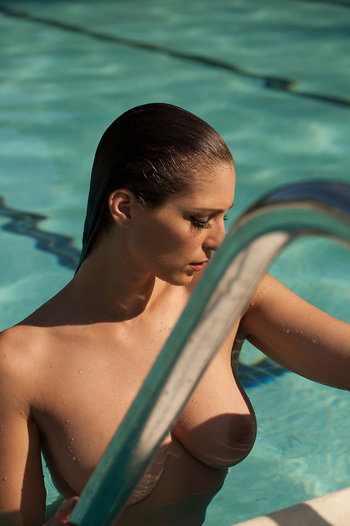 Nude woman emerging from swimming pool on pool ladder