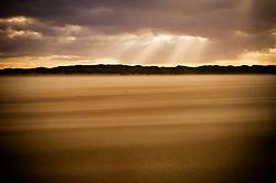Sand blows across the beach at Burnham Overy Staithe, North Norfolk Coast, England, UK.