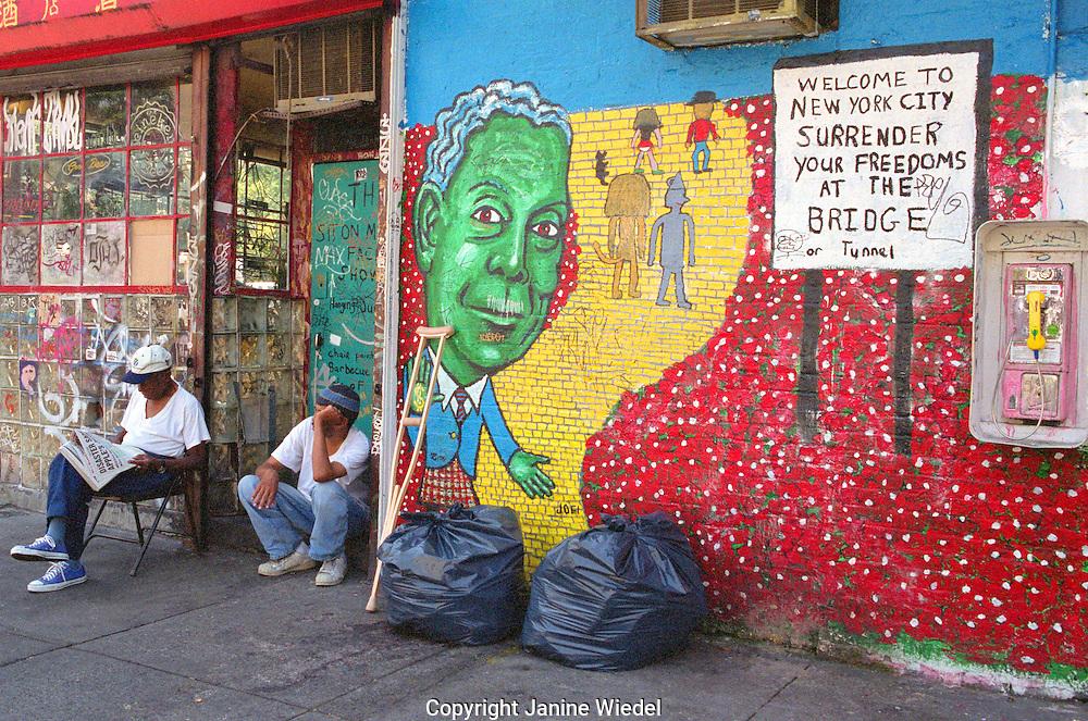 Homeless man sitting against graffiti wall on Manhattans lower Eastside.