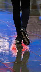 A woman splashes across the wet pavement at Piccadilly circus, with the famous illuminated billboard's lights reflected in the puddles. As forecasters predicted, the rain arrives in London where Londoners and tourists go about their business. London, February 13 2018.