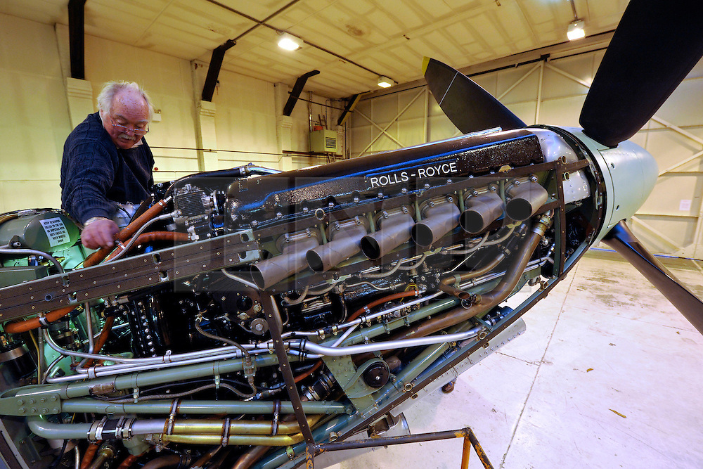 """© Licensed to London News Pictures. File picture dated 13/12/2012. Bristol, UK. Peter Dean works on a Rolls-Royce Merlin engine. Engineers race to finish work rebuilding a Mark IX Spitfire fighter circa 1943, at Filton airfield near Bristol. The plane has been rebuilt  by John Hart engineering, it is the last plane to be completed at the airfield and was flown out on 18 December 2012 by pilot Bill Perrins. Filton, the birthplace of the British-built Concorde jets, is to close on Friday (21st December 2012). Its owner BAE Systems says it is not viable and intends to sell it for housing and business development. BAE Systems said the airfield was closing following a comprehensive assessment over a five-year period and an independent review, """"both of which concluded that the airfield was not economically viable"""".  Airbus has said it is fully committed to the Filton site, where it has a base making aircraft wings.  A spokesman said: """"The closure of the airfield will have no significant effect on our business and we have mitigation plans in place regarding the change of venue for our passenger shuttle (using Bristol airport) and the transportation of the A400M wings (via Portbury docks).  Planes currently based at Filton will have to find new homes.The airfield officially closes for flights this Friday, though the police helicopter will still be based there. BAE is supporting a new museum at Filton to """"house Concorde Alpha-Foxtrot and Bristol's aviation heritage."""".Photo credit : Simon Chapman/LNP"""