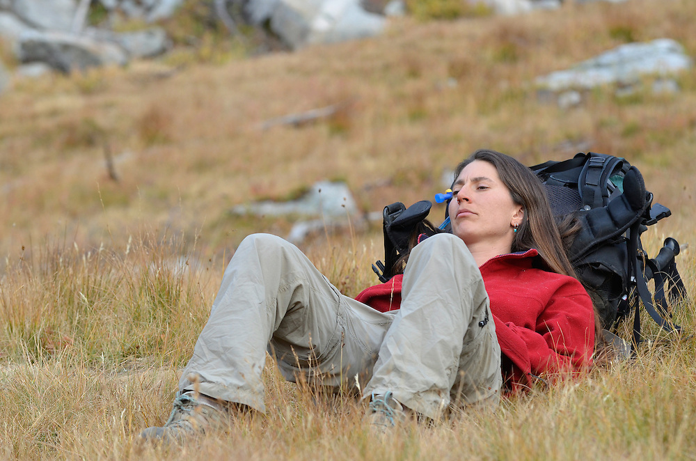 Backpacker resting against her backpack in a meadow high in Oregon's Wallowa Mountains.