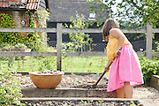 Charlotte, 6, rakes a bed in the vegetable garden at Hares Farm. CREDIT: Vanessa Berberian for The Wall Street Journal<br /> UKFARM-Hares Farm