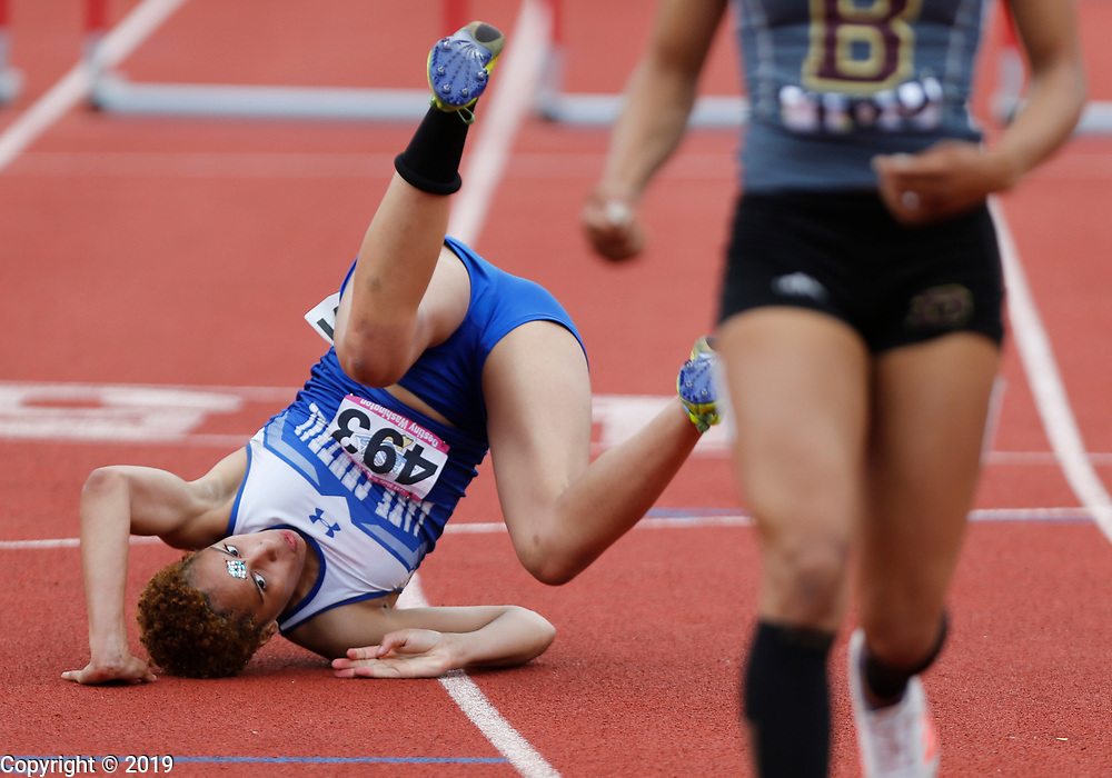 Lake Central's Destiny Washington tumbled at the end of the 100 hurdles final but still managed to win, and break the state record during the girls state track finals, Saturday, June 1, 2018 in Bloomington, Ind.