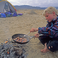 A youngster fries bacon over a campfire in Eureka Valley, part of California's Death Valley National Park.
