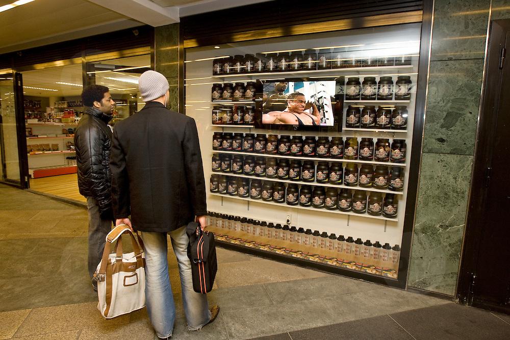 Nederland Rotterdam 27 maart 2009 20090327 Foto: David Rozing ..2 mannen bekijken reclame filmpje getoond in etalage body building zaak,  massieve krachtpatser in de gewichten om kracht -  preparaten aan te prijzen. .Men looking at commercial with bodybuilder, intended to sell power - food / nutrition..Foto: David Rozing