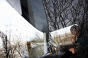 A lorry driver reads a newspaper and eats an apple for lunch in his cab at a drivers' layby on the A229 near Whitstable, Kent