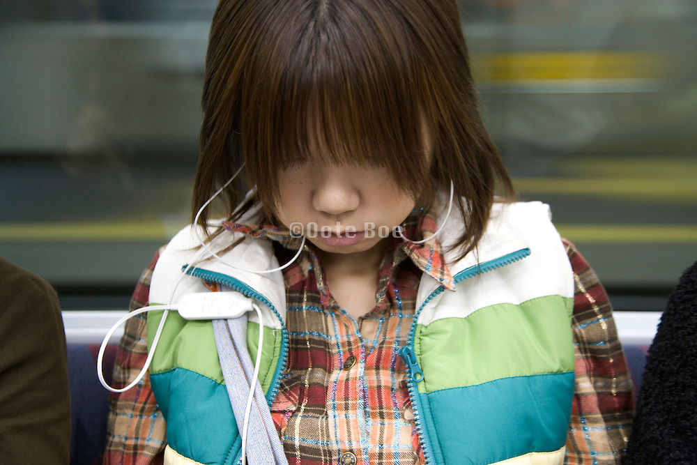 young girl reading and listening to music while traveling on a train Japan Tokyo