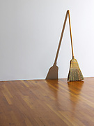 A straw broom leaning against and casting a shadow against a white wall