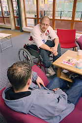 Two young men; one a wheelchair user; sitting talking in reception of day centre for homeless and vulnerably housed young people,