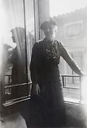 woman standing by an open window France