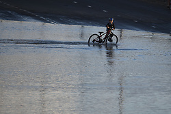 © Licensed to London News Pictures. 06/07/2020. London, UK. A boy rides his bike through severe flooding on the North Circular road at Brent Cross in North London where passengers have been rescued from vehicles and cars are stranded. Photo credit: Ben Cawthra/LNP