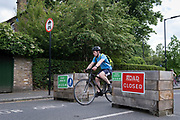 A cyclist passes through the barriers that form an LTN (Low Traffic Neighbourhood), an experimental closure by Southwark Council preventing motorists from accessing the junction of Carlton Avenue and Dulwich Village. Restrictions also prevent traffic from passing through at morning and afternoon rush-hour times in the borough of Southwark, on 14th June 2021, in London, England.