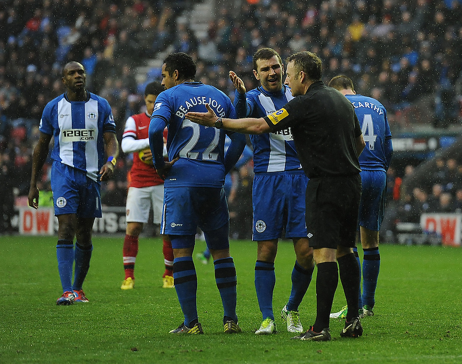 Wigan Athletic's James McArthur expresses his displeasure to Referee Jonathan Moss after he awarded a penalty kick for a foul by his with team-mate Jean Beausejour (L) on Arsenal's Theo Walcott. Arsenal's Mikel Arteta converted the penalty for the only goal of the match..Football - Barclays Premiership - Wigan Athletic v Arsenal - Saturday 22nd December 2012 - DW Stadium - Wigan..