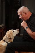 USA, Oregon, Keizer, man and Labrador Retriever bonding over pumpkin spice dog treats. MR, PR