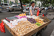 A fruit vendor along a busy road in Beijing, China