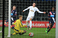 Owain Jones of Swansea city shoots past Newcastle goalkeeper Nathan Harker to score his teams 5th goal to make it 5-2. U21 Barclays Premier league match, Swansea city U21's  v Newcastle Utd U21's at the Liberty Stadium in Swansea, South Wales on Monday 4th April 2016.<br /> pic by Andrew Orchard, Andrew Orchard sports photography.
