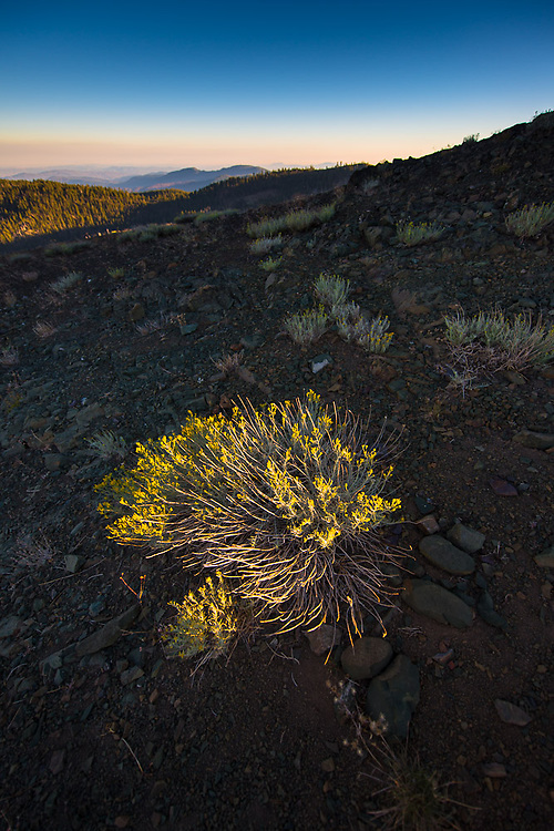 Last light is filtered through local wildfires, highlighting yellow bush on the dry peak of Snow Mountain.