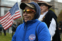 """November 20, 2018 - Philadelphia, Pennsylvania, US - A woman  attending a """"We The People"""" rally in Philadelphia smiles as a man waves an American flag at counter-protesters including anti-fascist or """"Antifa"""" members  on November 17th. The rally organizers said the demonstration was for militias members, gun lovers and patriots, though the event also drew  some members of the """"Proud Boys,"""" which the Southern Poverty Law Center has designated as a hate group. (Credit Image: © Miguel Juarez Lugo/ZUMA Wire)"""