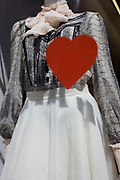 The shape of a red heart seen against a mannequin's dress in New Bond Street, central London. The detail of the mannequin's dress and top are in the background of the out of focus heart, the human organ seen in its proper place on the body. Representing the human soul or humanity itself, it is a scene of fashion, the beating heart and of affection and fondness.