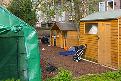 A small wooden wendy house, background, in a section of an allotment reserved as a children's play area appears to have become the residence or storage shed of a homeless individual, whilst the adjacent shed, right, appears to have had its lock forced. Munster Square, Camden, March 18 2019.