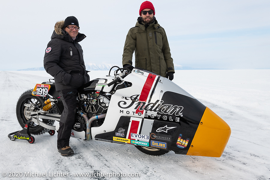 Belgian custom bike builder Brice Hennebert (red hat) with Brices's Appaloosa 2018 Indian Scout Bobber racer and French pilot Sebastien Lorentz at the Baikal Mile Ice Speed Festival. Maksimiha, Siberia, Russia. Wednesday, February 26, 2020. Photography ©2020 Michael Lichter.