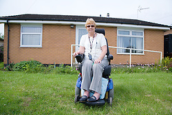 Female wheelchair user outside her house; concrete ramp and grab rails in the background,
