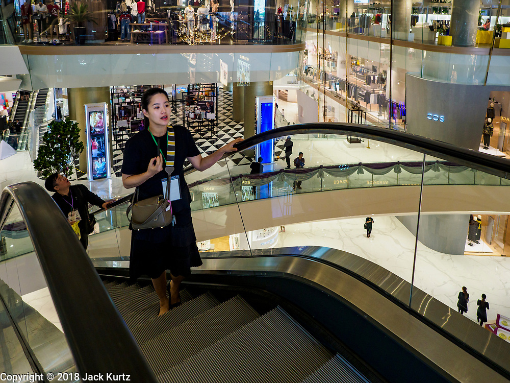 09 NOVEMBER 2018 - BANGKOK, THAILAND: One of the first people into ICONSIAM rides an escalator up to the third level of the mall. ICONSIAM opened November 9. ICONSIAM is a mixed-use development on the Thonburi side of the Chao Phraya River. It includes two large malls, with more than 520,000 square meters of retail space, an amusement park, two residential towers and a riverside park. It is the first large scale high end development on the Thonburi side of the river and will feature the first Apple Store in Thailand and the first Takashimaya department store in Thailand.   PHOTO BY JACK KURTZ