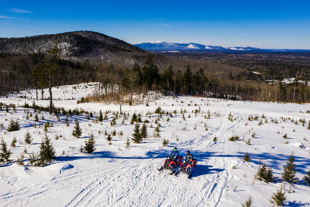 Snowmobiling from Shin Pond Village near Maine's Katahdin Woods and Waters National Monument. The Traveller Mountain range is in the distance.