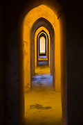 Long corridor of repeating pointed arches in the underground of the Alcazar besides the Baths of Dona Maria de Padilla, Sevilla, Andalusia, Spain.