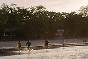 Four male Indonesian surfers run towards the sea at Batu Karas beach on the 31st October 2019 in Java in Indonesia.
