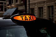 London taxi cab sign is lit up to show that it is available.