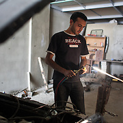 Ali works on a car helped by his assistant in the garage owned by the Mayor of Mdoukha. Ali Abed el Razzak Zamzam, 29, is from Zamalka in Syria. He came to Mdoukha with his fiancé after life in the town got too dangerous because of fighting, most of the time they had to stay in a shelter with no food,water or electricity because of heavy Government shelling and tanks destroyed his grandparents house. <br /> Ali now works as a mechanic in a garage owned by the local Mayor and he lives in an unfinished building owned by the Mayor with his fiancé and her family. The Mayor takes half of what Ali makes and has lend him money to buy house hold equipment. He has been in Lebanon for a year and misses his family who are all back in Syria, - all wants is the war to stop so he can go back, marry his fiancé and have children.