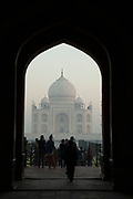 The Taj Mahal on a misty sunrise through an entrance arch with crowds in silhouette in the foreground