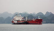 Oil Tanker FPMC 17, pausing for refuelling in front of misty limestone karsts and islands in Ha Long Bay, near Cat Ba Island, Vietnam