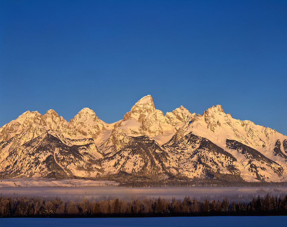 """Winter sunrise on the Teton Range is a mountain range of the Rocky Mountains in North America. A north-south range, it is on the Wyoming side of the state's border with Idaho, just south of Yellowstone National Park. Most of the range is in Grand Teton National Park.<br /> <br /> Early French Voyageurs used the name """"les Trois Tétons"""" (the three breasts).[1] It is likely that the Shoshone people once called the whole range Teewinot, meaning """"many pinnacles"""".[2]<br /> <br /> The principal summits of the central massif, sometimes referred to as the Cathedral Group, are Grand Teton (13,770 feet (4,200 m)), Mount Owen (12,928 feet (3,940 m)), Teewinot (12,325 feet (3,757 m)), Middle Teton (12,804 feet (3,903 m)) and South Teton (12,514 feet (3,814 m)). Other peaks in the range include Mount Moran (12,605 feet (3,842 m)), Mount Wister (11,490 feet (3,500 m)), Buck Mountain (11,938 feet (3,639 m)) and Static Peak (11,303 feet (3,445 m))."""
