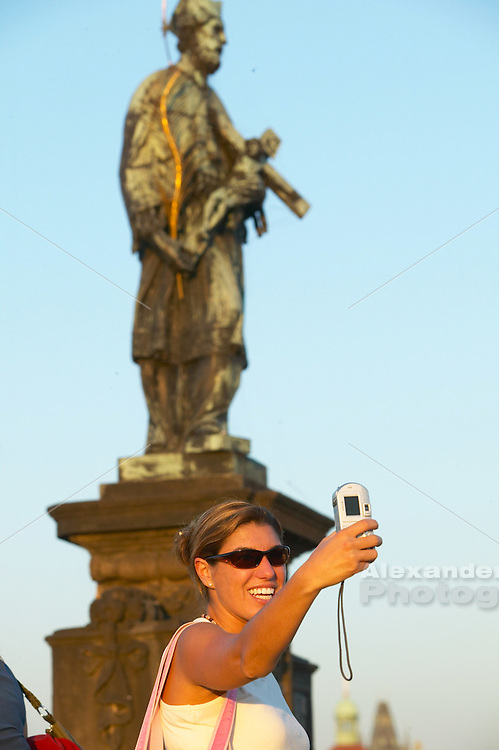 Czeck Republic - Prague, young woman takes a self portrait of the Charles Bridge