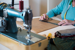 Old woman measuring with a ruler on sewing desk