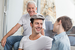 Happy grandfather, father and son at home