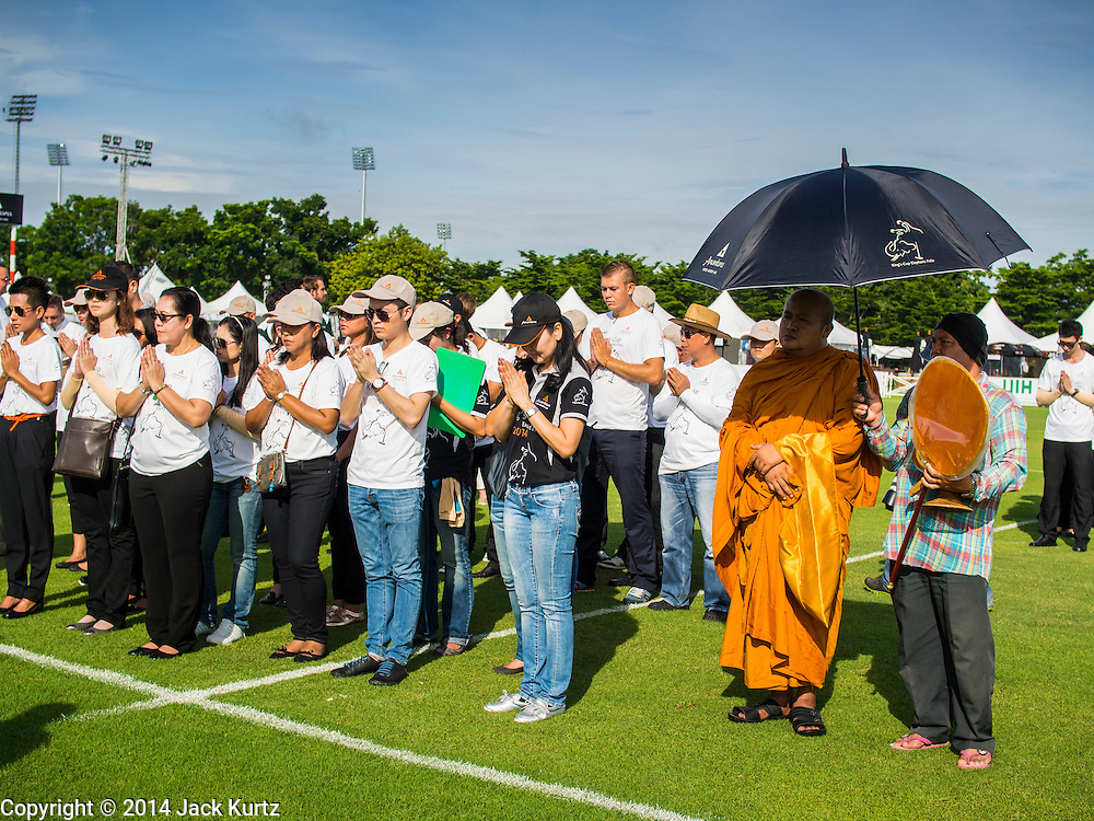 """28 AUGUST 2014 - BANGKOK, THAILAND:     A Buddhist monk (right) stands under an umbrella for shade while others pray at a blessing ceremony before the King's Cup Elephant Polo Tournament at VR Sports Club in Samut Prakan on the outskirts of Bangkok, Thailand. The tournament's primary sponsor in Anantara Resorts. This is the 13th year for the King's Cup Elephant Polo Tournament. The sport of elephant polo started in Nepal in 1982. Proceeds from the King's Cup tournament goes to help rehabilitate elephants rescued from abuse. Each team has three players and three elephants. Matches take place on a pitch (field) 80 meters by 48 meters using standard polo balls. The game is divided into two 7 minute """"chukkas"""" or halves.  PHOTO BY JACK KURTZ"""