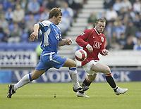 Photo: Aidan Ellis.<br /> Wigan Athletic v Manchester United. The Barclays Premiership. 14/10/2006.<br /> united's Wayne Rooney battles with Wigan's Arjun De Zeuuw