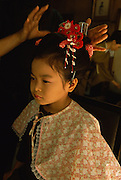 A girl has her hair fixed in traditional style for her shichi-go-san in Tokyo, Japan. During shichi-go-san, literally seven-five-three, parents dress their daughters aged three and seven and sons aged five in traditional costume and take them to a Shinto shrine to be blessed.