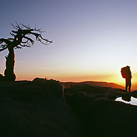 Hikers watch a sunset from Sentinel Dome, Yosemite National Park.